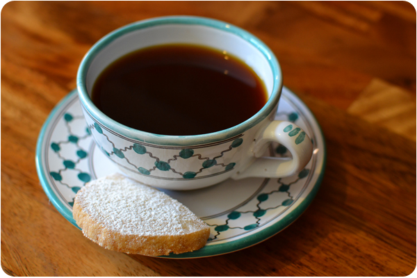 cup of black coffee with homemade biscuit on the saucer